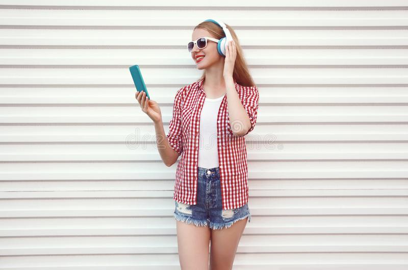 La giovane donna sorridente felice in cuffie con lo smartphone che ascolta la musica che porta la camicia a quadretti, mette su b immagine stock libera da diritti