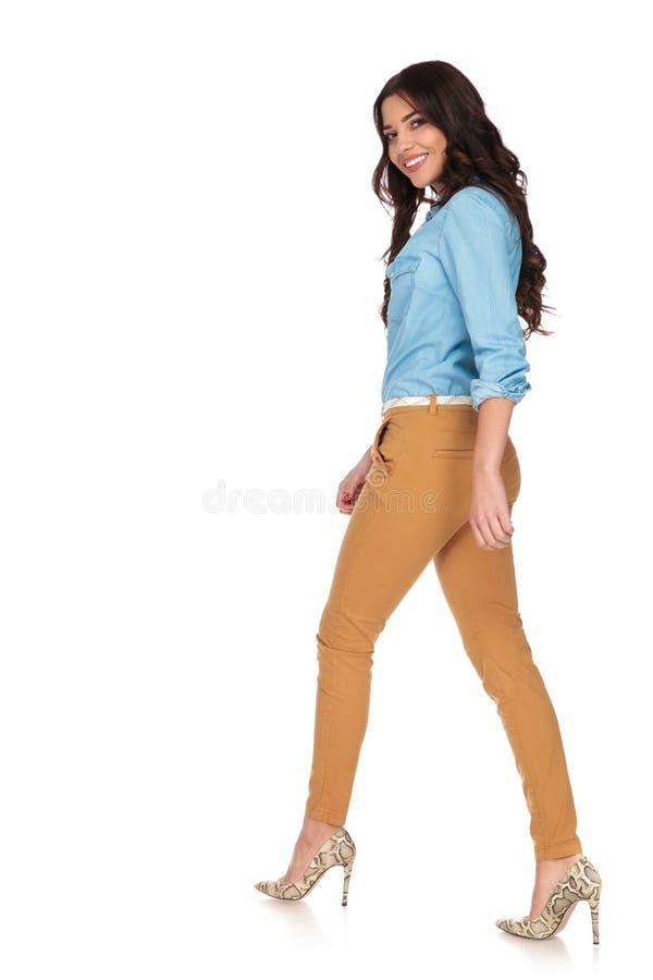 La giovane donna sorridente guarda indietro sopra la sua spalla mentre cammina fotografia stock libera da diritti