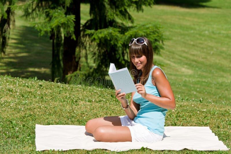 La giovane donna sorridente ha letto il libro in sosta fotografia stock