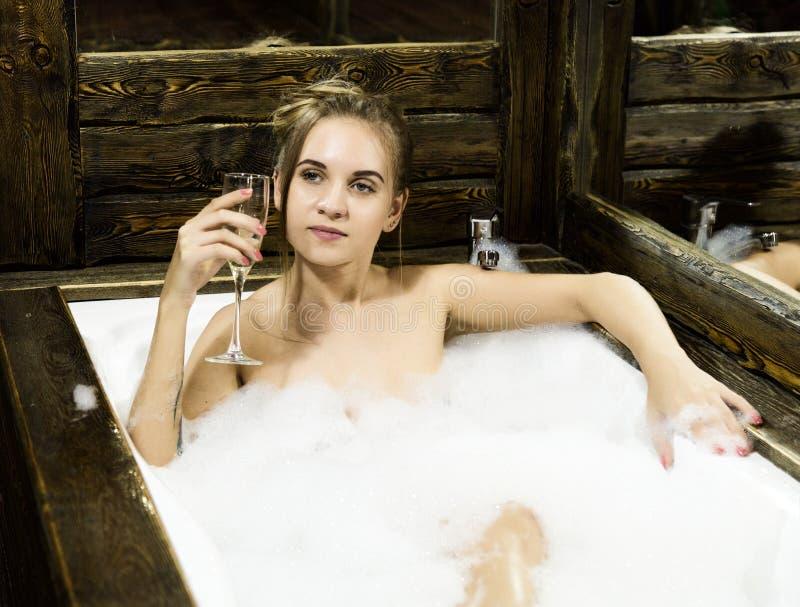 La giovane donna sorridente nuda con capelli lunghi e diritto dimagrisce il bello ente che si trova in vasca da bagno bianca dell fotografia stock libera da diritti
