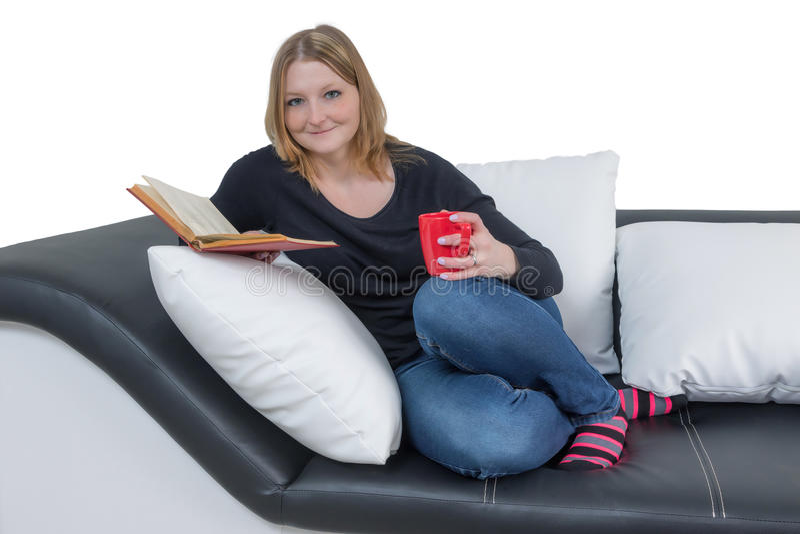 La giovane donna sorridente sta leggendo un libro fotografie stock libere da diritti
