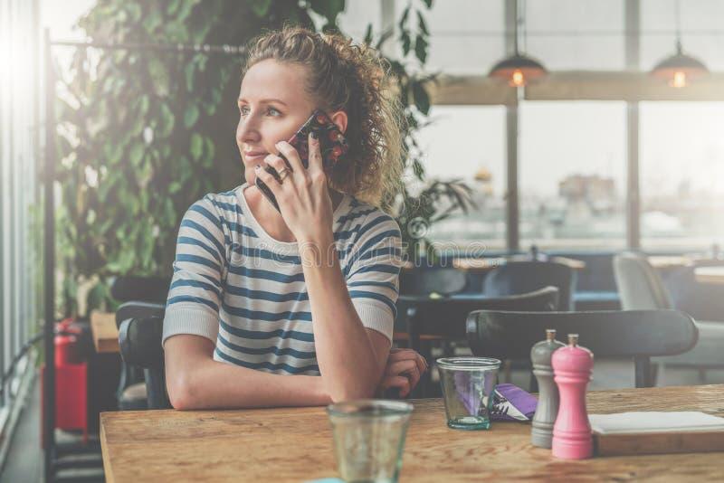 La giovane donna sorridente sta sedendosi in caffè alla tavola di legno e sta parlando sul telefono cellulare immagini stock