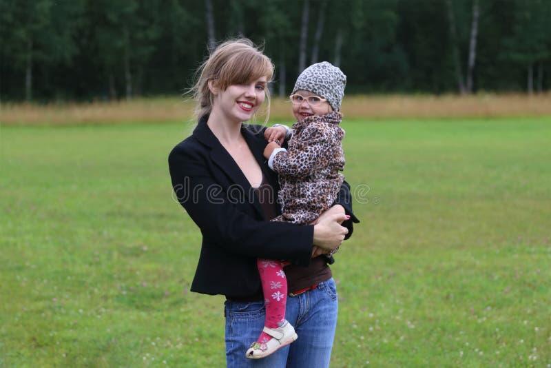 La giovane donna sorridente tiene la piccola figlia fotografia stock libera da diritti
