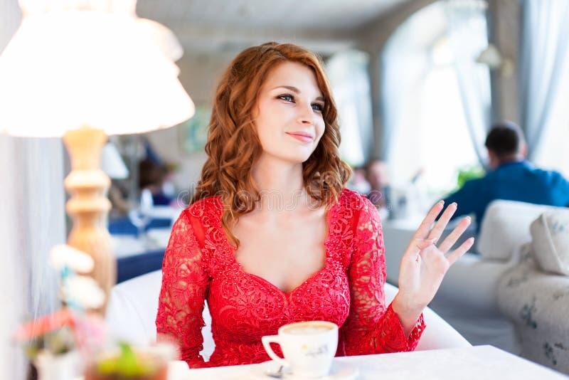 La giovane donna sorridente in vestito rosso sta aspettando un cameriere fotografie stock libere da diritti