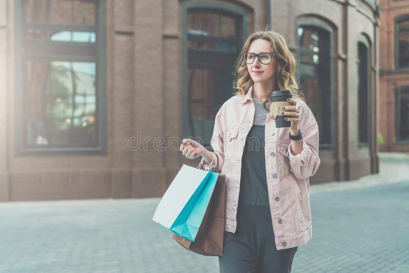 La giovane donna sorridente in vetri porta i sacchetti della spesa e tiene la tazza di caffè La ragazza ha comprato i presente pe fotografia stock