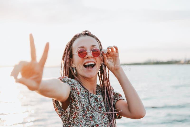 La giovane donna spensierata felice con le trecce africane in occhiali da sole rotondi rosa gode della sua vita sulla spiaggia, l immagine stock
