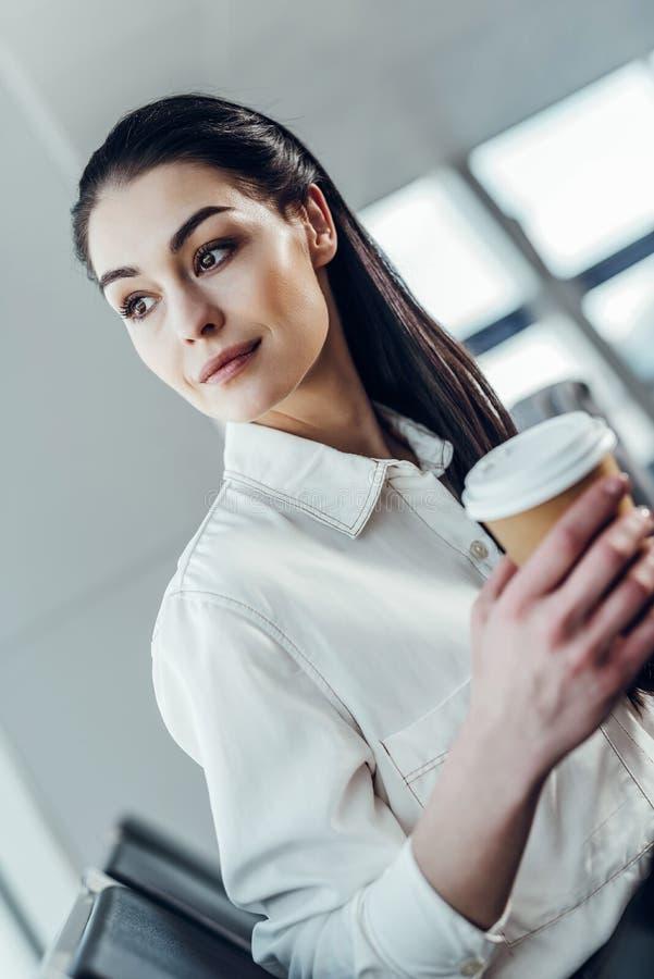 La giovane donna spensierata sta avendo bevanda calda in aeroporto immagini stock libere da diritti