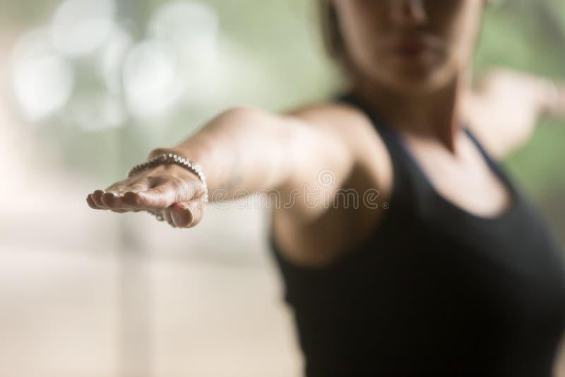 La giovane donna sportiva in guerriero due posa, fondo dello studio immagine stock