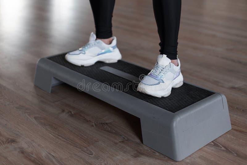 La giovane donna sportiva in scarpe da tennis bianche alla moda in ghette si accovaccia sui punti della piattaforma nella palestr fotografia stock libera da diritti