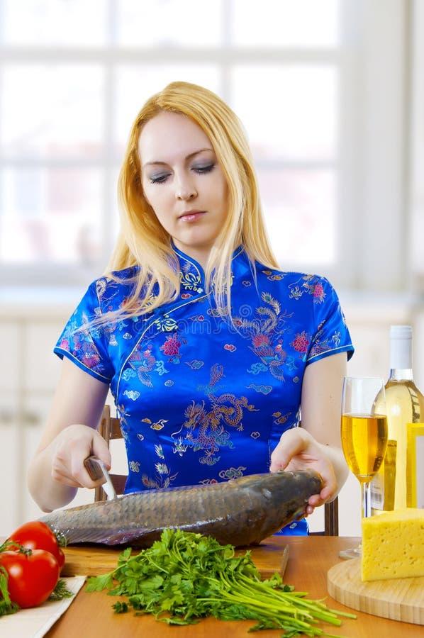 La giovane donna sta cucinando i pesci freschi in cucina fotografia stock libera da diritti