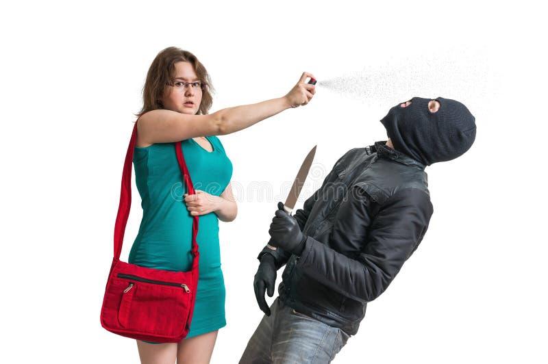 La giovane donna sta difendendo con spray al pepe contro il ladro munito con il coltello immagine stock libera da diritti