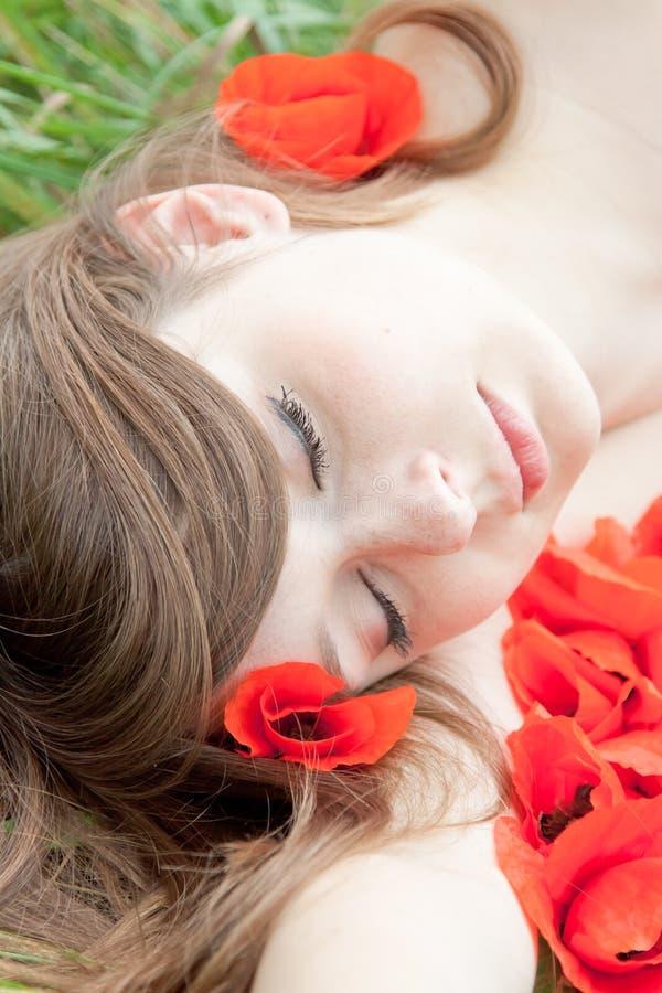 La giovane donna sta dormendo - fronte sui fiori rossi immagini stock libere da diritti