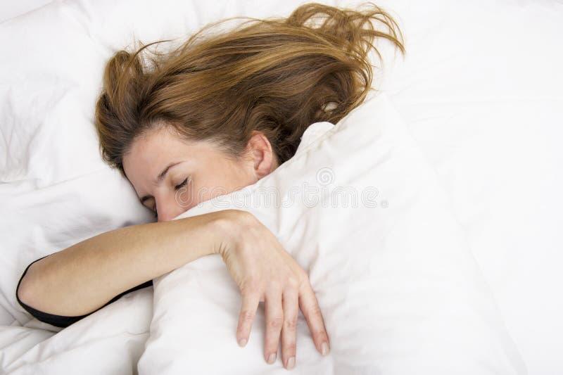 La giovane donna sta dormendo nel suo letto immagine stock libera da diritti