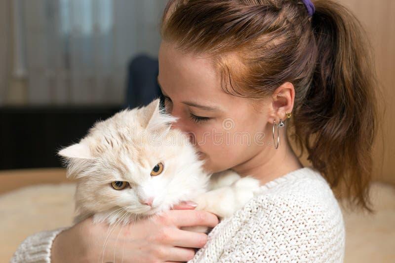 La giovane donna sta giocando con il suo gatto fotografie stock libere da diritti