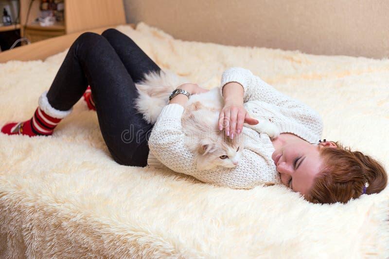 La giovane donna sta giocando con il suo gatto fotografie stock