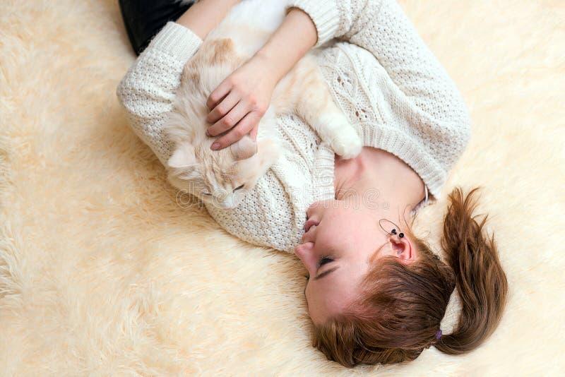 La giovane donna sta giocando con il suo gatto fotografia stock