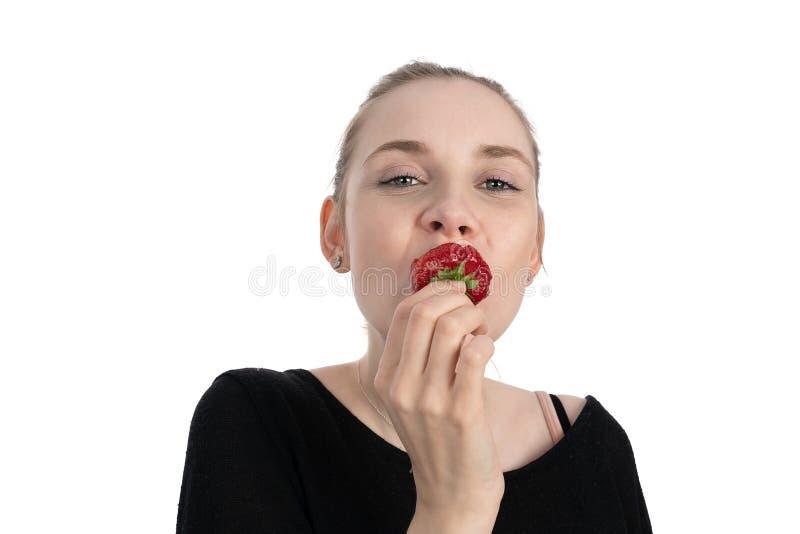La giovane donna sta godendo di di mangiare una fragola immagine stock