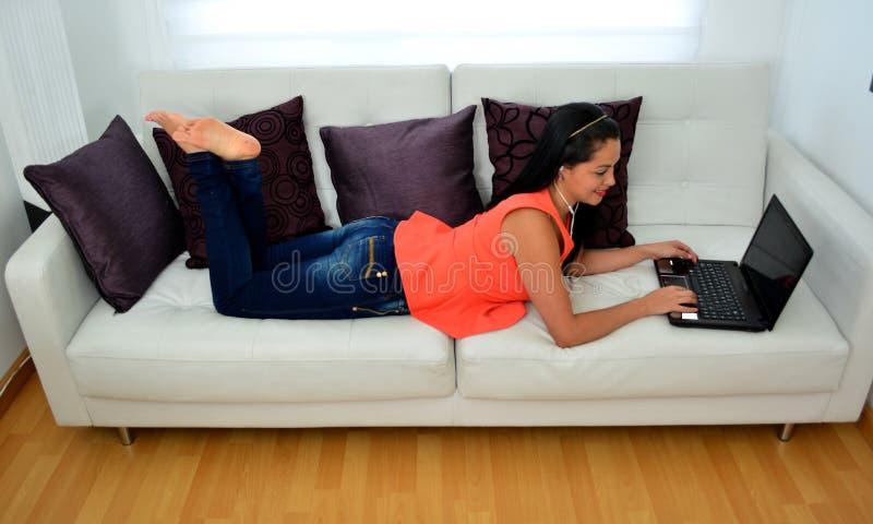 La giovane donna sta lavorando ad un computer portatile fotografia stock libera da diritti