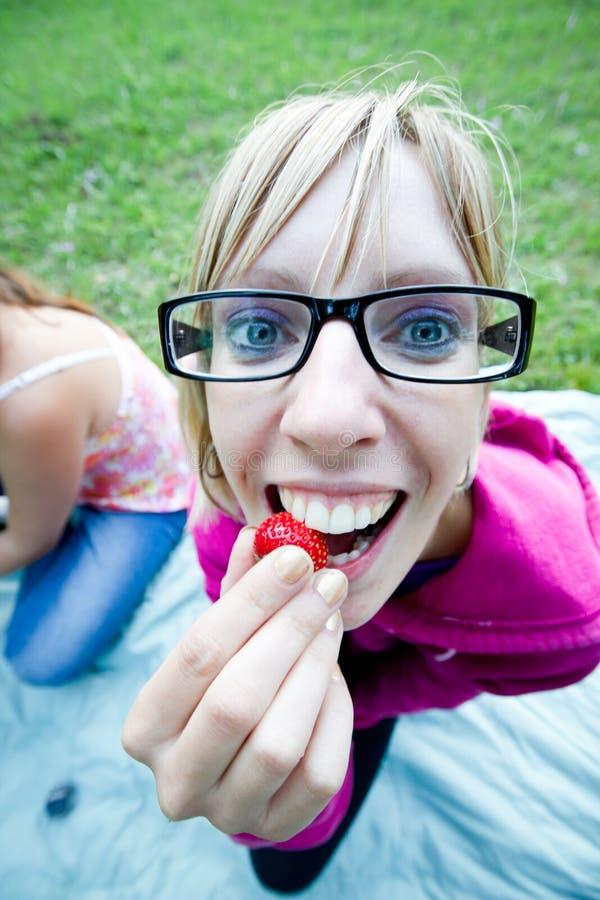 La giovane donna sta mangiando la fragola fotografie stock