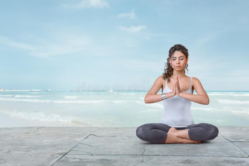 La giovane donna sta meditando su spiaggia immagine stock
