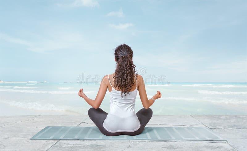 La giovane donna sta meditando su spiaggia fotografia stock libera da diritti