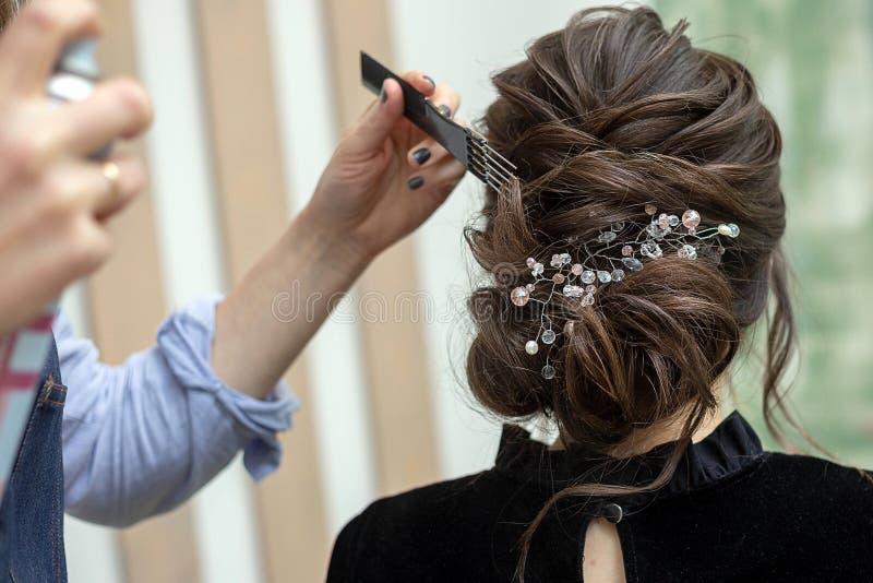 La giovane donna sta ottenendo un taglio di capelli ad un salone immagine stock