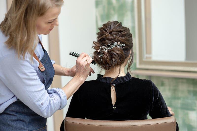 La giovane donna sta ottenendo un taglio di capelli ad un salone fotografia stock libera da diritti