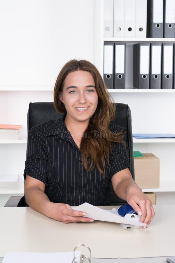 La giovane donna sta perforando i documenti immagini stock