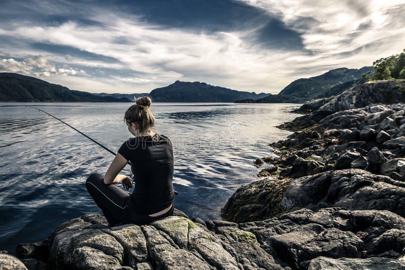 La giovane donna sta pescando in Norvegia immagini stock libere da diritti