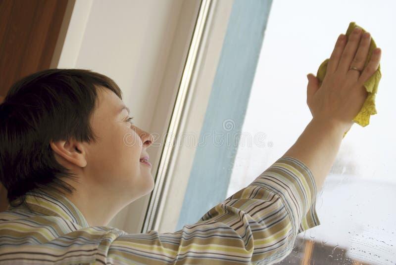 La giovane donna sta pulendo una finestra immagine stock libera da diritti