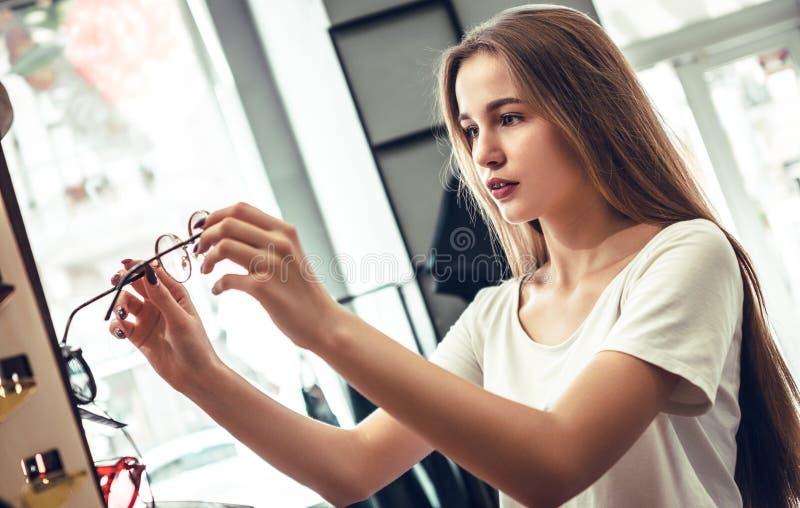La giovane donna sta scegliendo i vetri nel deposito dell'ottico fotografie stock