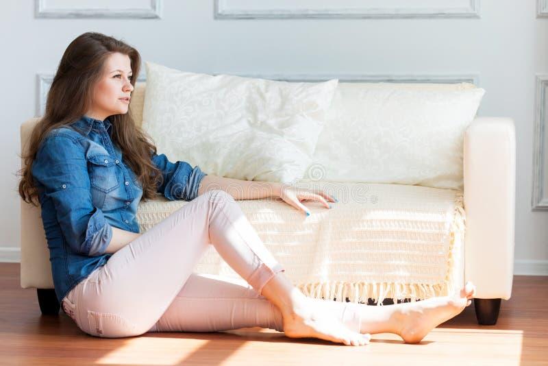 La giovane donna sta sedendosi sul pavimento vicino al sofà fotografie stock