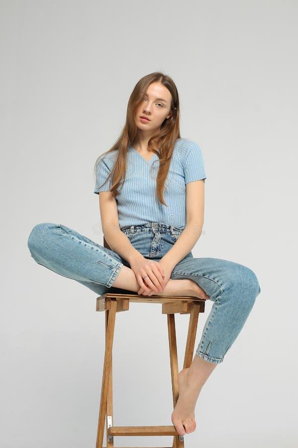 La giovane donna sta sedendosi sulla sedia di legno in studio fotografia stock libera da diritti