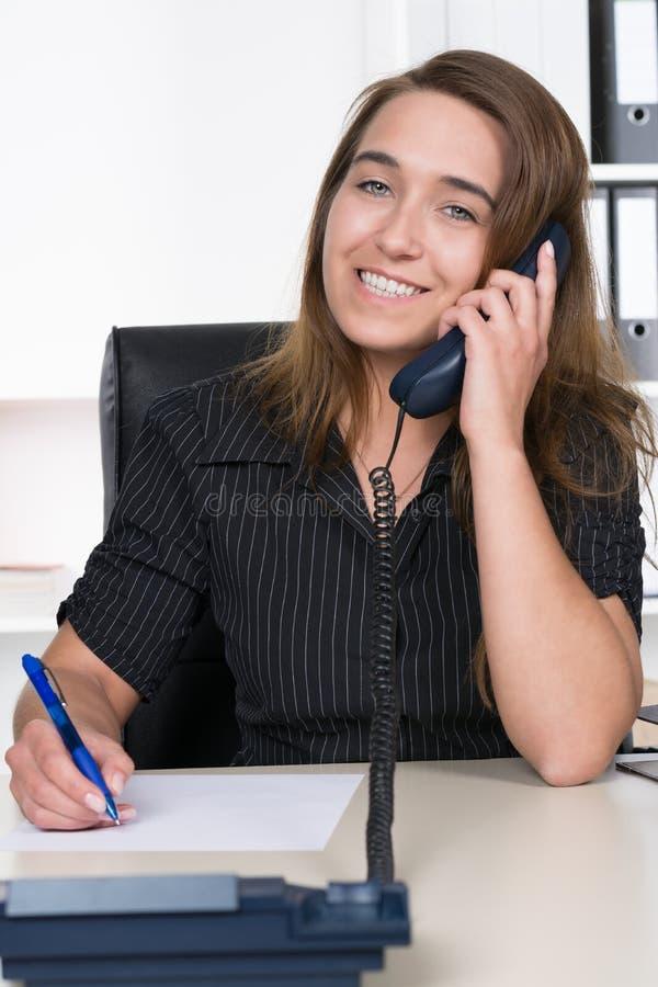 La giovane donna sta telefonando nell'ufficio immagini stock