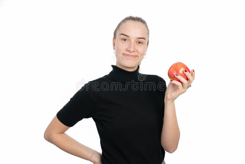 La giovane donna sta tenendo una mela nella nel suoi mano e sorridere fotografia stock libera da diritti