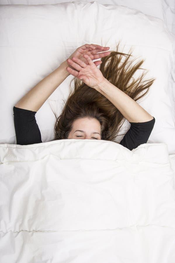 La giovane donna sta trovandosi nel suo letto con gli occhi chiusi, sorridenti sotto la sua coperta dopo un sonno riposante fotografie stock libere da diritti
