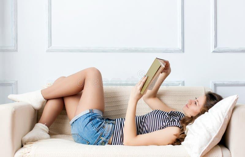 La giovane donna sta trovandosi sul sofà fotografie stock libere da diritti