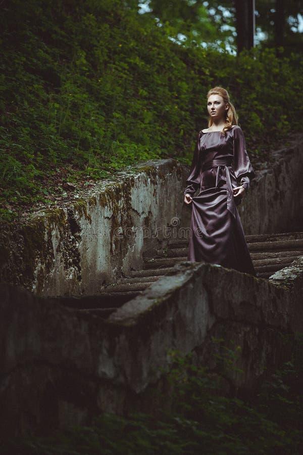 La giovane donna su una scala nel legno fotografie stock libere da diritti