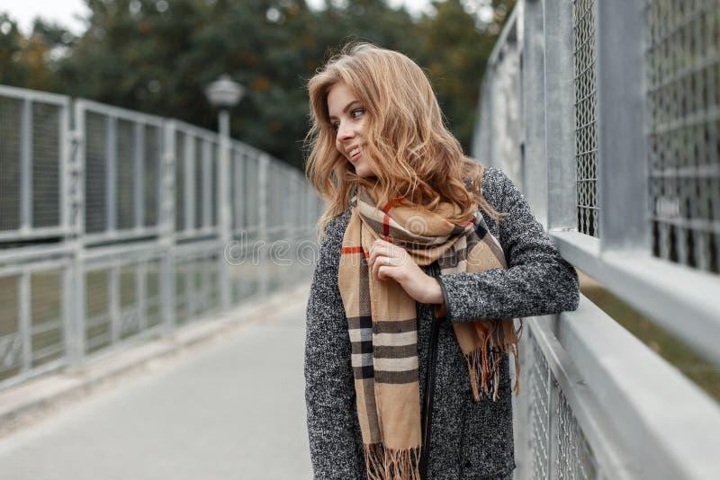 La giovane donna sveglia graziosa felice in un cappotto alla moda di autunno d'annata in una sciarpa beige alla moda sta stando a immagini stock