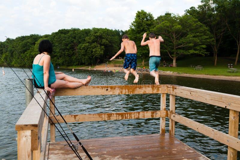 La giovane donna tiene i suoi occhi sui bambini mentre essi che saltano nel lago fotografie stock libere da diritti