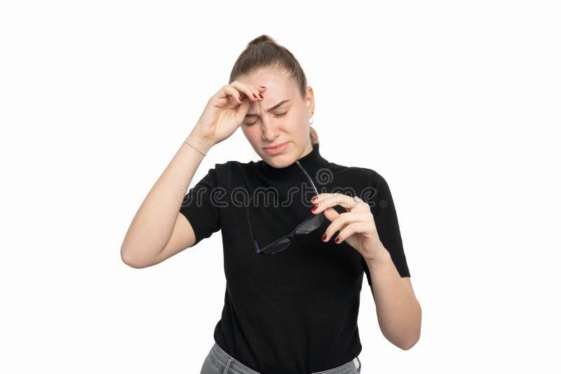 La giovane donna tiene i suoi vetri nella sua mano ed in un'emicrania fotografia stock libera da diritti