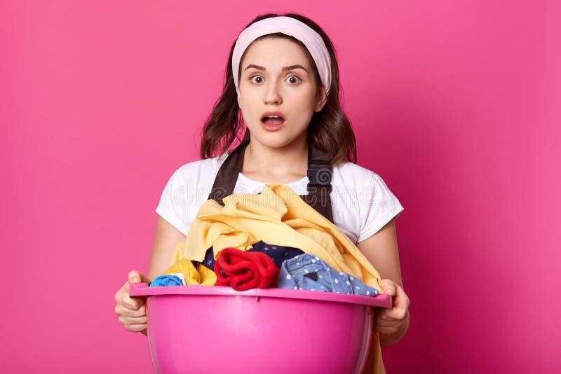 La giovane donna tiene il bacino in pieno di tela pulita, casalinga sembra stanca dopo avere fatto la lavanderia, impianti circa  fotografia stock