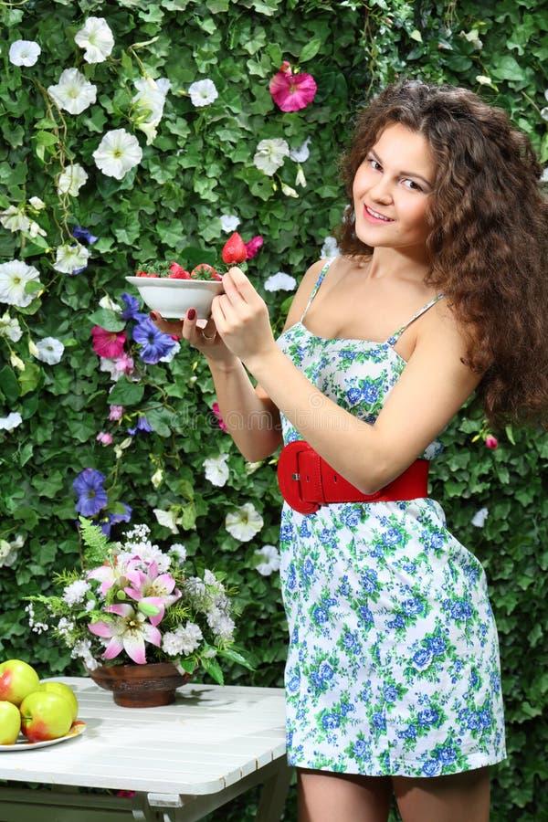 La giovane donna tiene il piatto con le fragole e mostra una bacca fotografia stock libera da diritti
