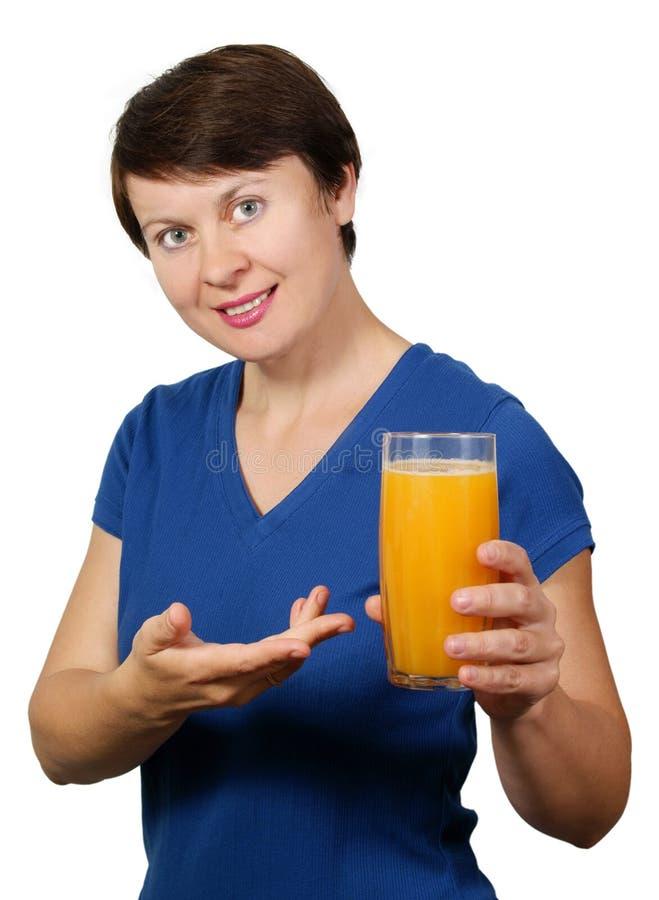 La giovane donna tiene un vetro del succo di arancia fotografia stock libera da diritti