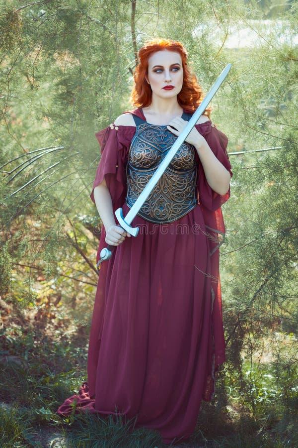 La giovane donna tiene una spada in sua mano fotografie stock