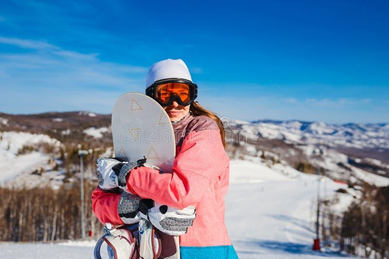 La giovane donna tiene uno snowboard sui pendii dello sci immagine stock libera da diritti