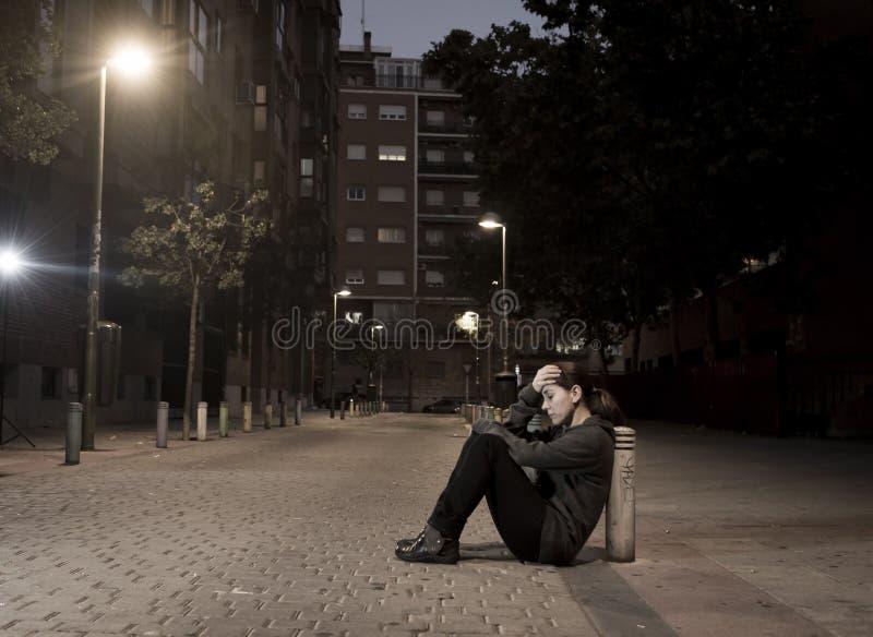 La giovane donna triste che si siede sulla via ha frantumato a disperato solo di notte fotografia stock