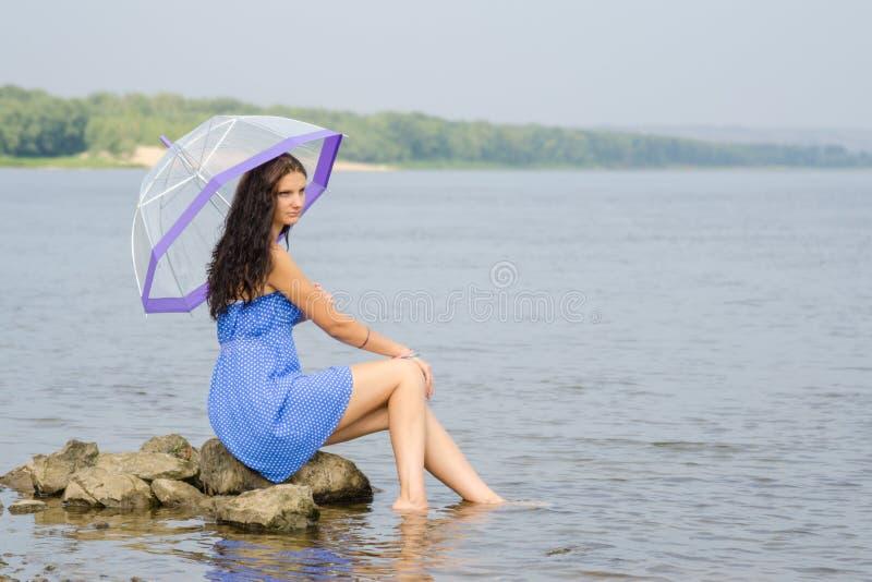 La giovane donna triste sola con un ombrello si siede su una roccia dal fiume fotografia stock libera da diritti