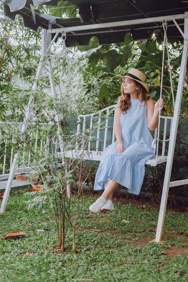 La giovane donna in un cappello si siede su un'oscillazione fotografie stock libere da diritti