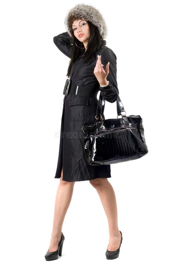 La giovane donna in un cappotto nero ed in una protezione della pelliccia fotografie stock